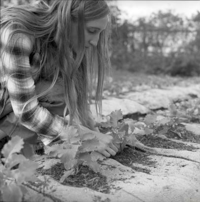 Farmer Becca demonstrating planting techniques.